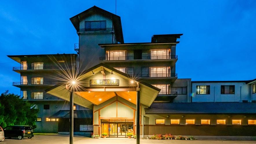 夕暮れ時の外観。広い玄関屋根が特徴的な当ホテルのトレードマークれ時