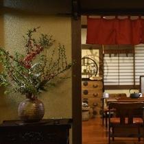 フロント横の生け花と奥は囲炉裏カフェ