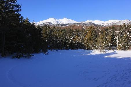 冬、雪に覆われた牛止めの池と乗鞍岳