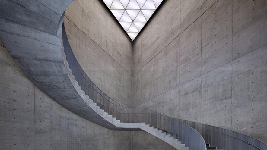 【秋田県立美術館】自然光が入る三角形の天井や天然御影石の床で構成された吹き抜けのホール。