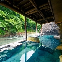 【お題目大露天風呂】四万川に面した、浴槽は長さ30mで開放感抜群。お題目を刻んだ大岩が目を引きます。