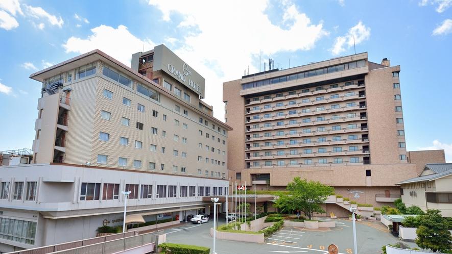 ■ホテル外観(昼):正面左側の建物が入口・フロント、隣の新館へはエスカレーターでつながっております。