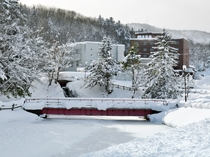 【外観】夏にはせせらぎが聞こえる宿沿いの川も厚い氷に覆われ、辺り一面が雪化粧を纏います。