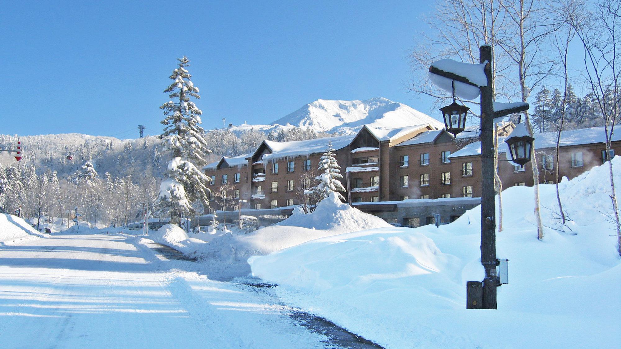 冬の旭岳をバックにたたずむベアモンテ