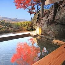 秋の貸切露天風呂風呂湯船に鮮やかな紅葉を映す
