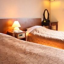 ベッドの間には2か所のコンセントがあって〇 ティッシュ、電気スイッチ、懐中電灯、時計も枕元にあります