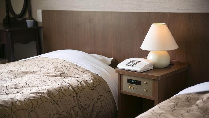 【洋室ツイン】サイドテーブルにアラーム機能付、さらにモーニングコールで二度寝予防対策も