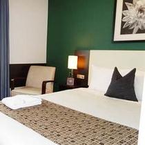 【シングルルーム】落ち着いた深緑の壁紙は筑波山をイメージ。