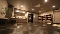 グランドアネックス館の男性大浴場脱衣場でございます。本館よりも広く、シック&モダンな脱衣場です。