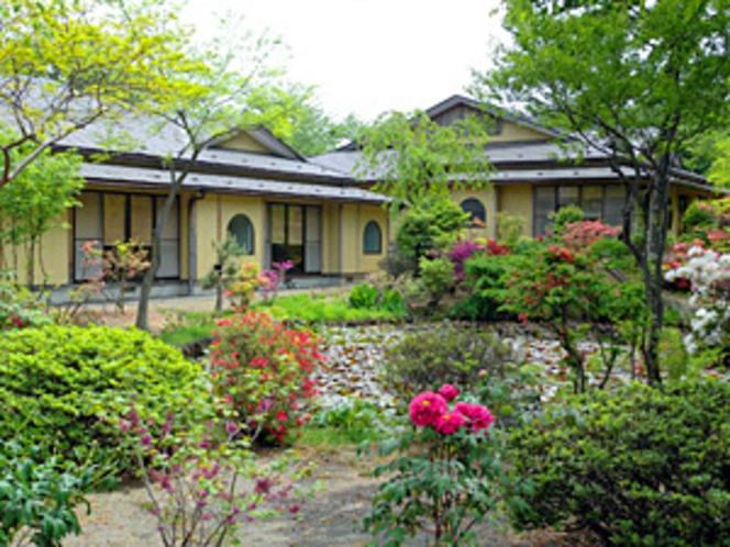 つつじが咲き誇る初夏の庭園から望む本館 外観