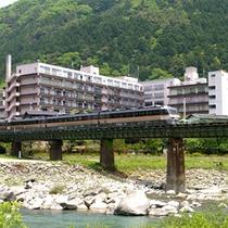飛騨川の上を走る高山本線を眺める望川館全景