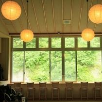 【休憩処】大きな窓が開放的。ソファやマッサージチェア、山を望むカウンターは休憩にぴったり。