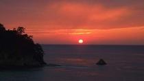 当館から見た沈み行く夕陽と三四郎島