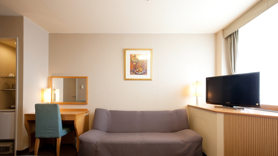 【ツイン】大きめな二人掛けソファをご用意しております。お寛ぎながらご旅行の語らいをお楽しみください。