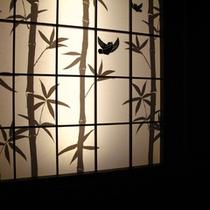 【すずめの湯入口】影絵風の竹林にすずめをあしらった照明。