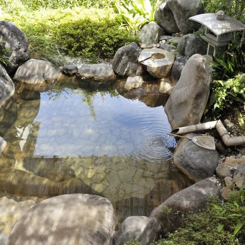 緑の中で静かに佇む岩露天風呂