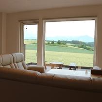 *プライベートハウス/リビングのソファに腰かけ、大きな窓の外に広がる富良野の絶景を堪能できます。