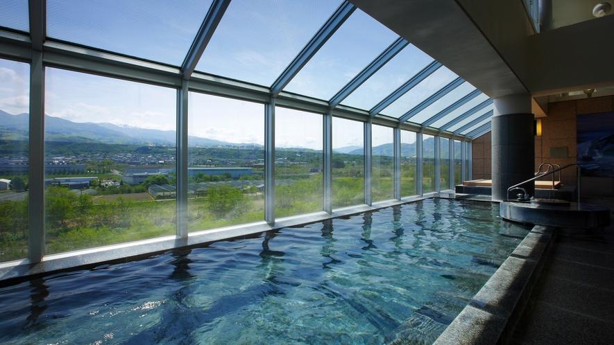 【大浴場】最上階にある広々とした大浴場。一面ガラス越しに壮大な蔵王連邦、山形の風景を望めます。