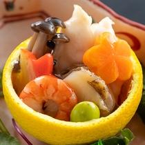 【柚子蒸し】河豚に海老、鮑を香り爽やかな柚子釜に盛りつけ優しい味わいの餡をかけた色鮮やかな創作料理