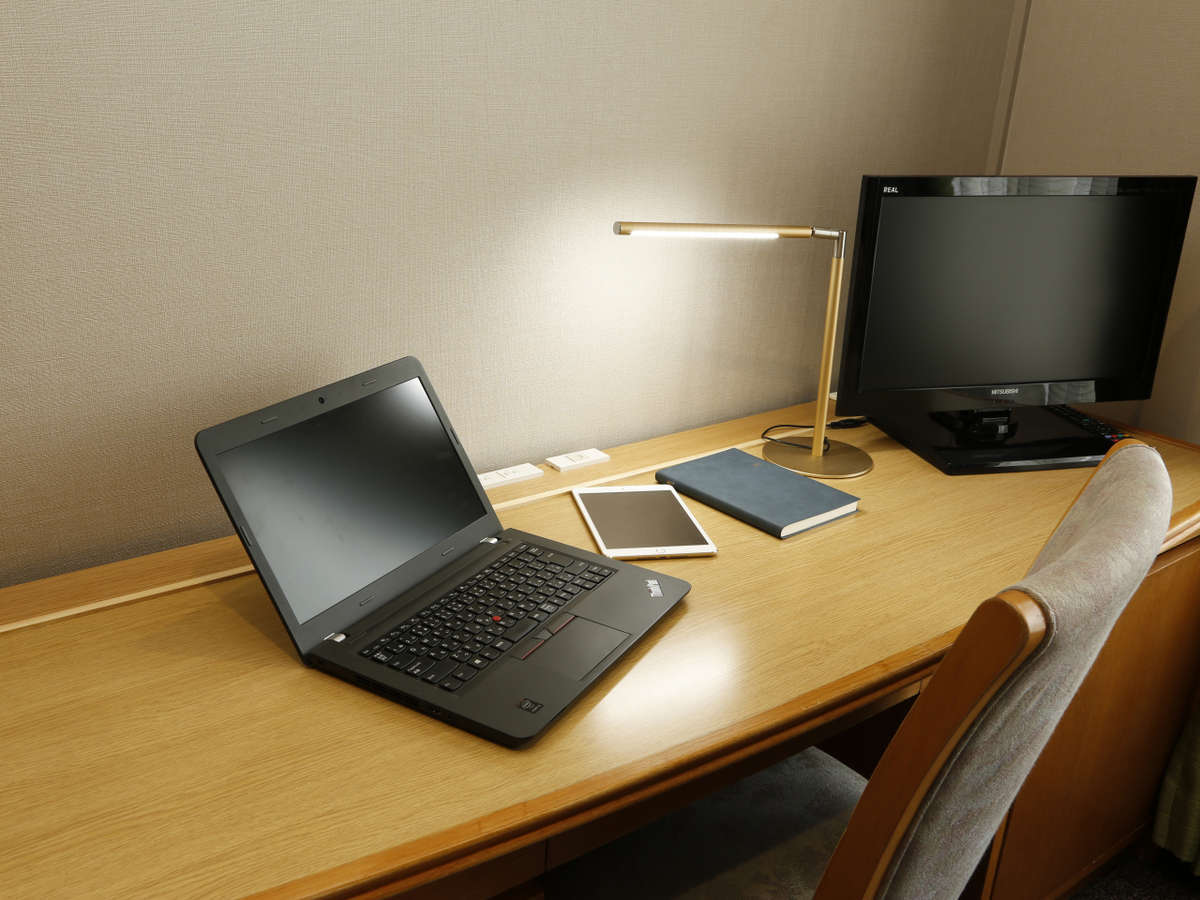 シングルルームのデスク使用イメージ。ノートPCを置いても余裕のある広いデスクでお仕事に最適です。