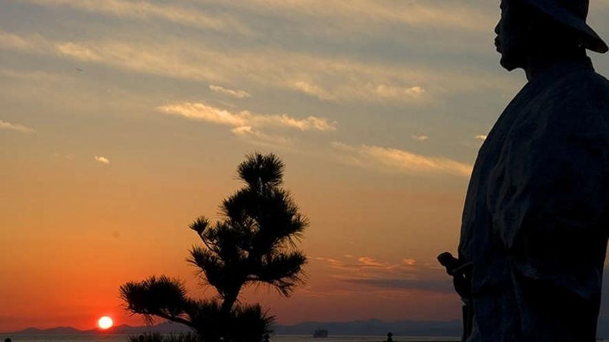 夕陽色に染まる土肥サンセットビーチとこの地で多くの作品を執筆した若山牧水像