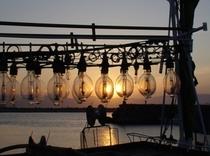 イカ釣り船のライトが夕日に染まる