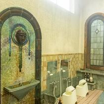 *【岩本楼ローマ風呂】人面のレリーフの周りに黄・緑・青のモザイク片が放射状に並んでいます。