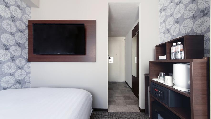【シングルルーム】TV画面は40インチ。シモンズ社製ベット下にはスーツケースなどを収納可能。