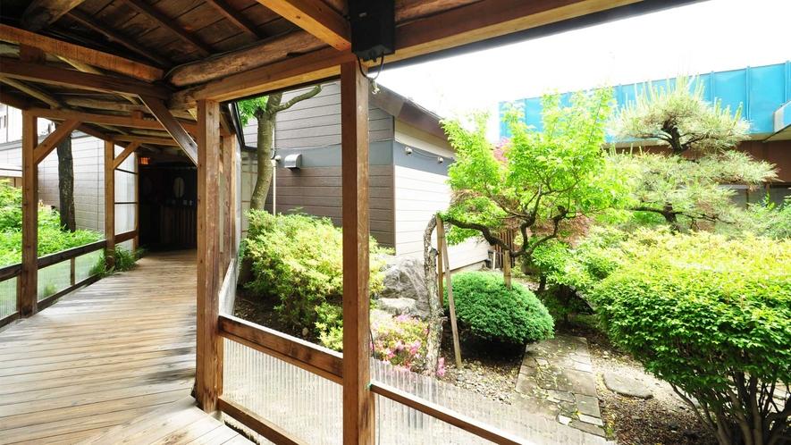 【炭の湯】大浴場へ続く渡り廊下では、趣ある中庭を眺めることができます。